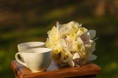 Teetassen und Blumenstrauß stockfotos