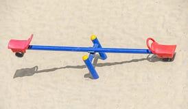 Teeter cambalea com cadeiras vermelhas, areia da praia, equilíbrio, fim acima Imagens de Stock Royalty Free