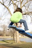 Teeter totter bounce. A young girl bouncing in the air on a teeter totter, or see saw, in a park Royalty Free Stock Image