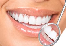 Teeth. Healthy woman teeth and a dentist mouth mirror Stock Photography