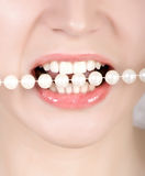 Teeth biting on faux pearls Royalty Free Stock Image