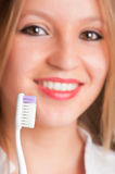 Teeth Brushing. Closeup of young woman with a tooth brush on her hands, about to brush her teeth Stock Image
