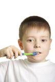 Teeth brushing. Serious boy in white t-shirt brushing teeth isolated stock image