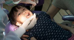 Teeth checkup at dentist`s office. Dentist examining asian girls stock photos