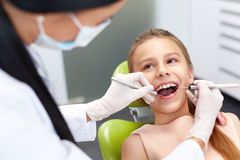 Teeth checkup at dentist's office. Dentist examining girls teeth. In the dentists chair royalty free stock image