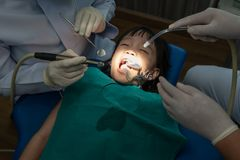 Teeth checkup at dentist`s office. Dentist examining girls teeth in the dentists chair stock photo