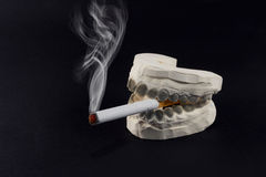 Teeth and cigarettes Stock Photography
