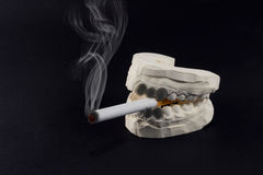 Teeth and cigarettes Royalty Free Stock Photo