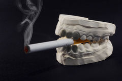 Teeth and cigarettes Stock Photos