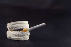 Teeth and cigarettes Royalty Free Stock Images