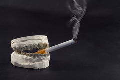 Teeth and cigarettes Royalty Free Stock Photos