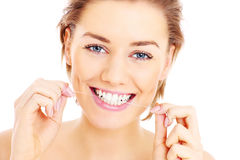 Teeth flossing. A picture of  beautiful woman flossing her teeth over white background Stock Photography