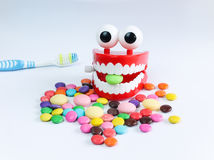Teeth mock up with toothbrush and colorful candies. Dental care concept Stock Images