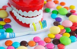Teeth mock up with toothbrush and colorful candies. Dental care concept Stock Image
