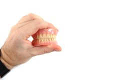Teeth prosthesis in human hand Royalty Free Stock Photo