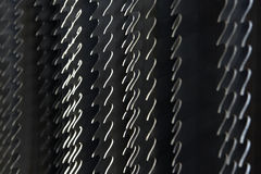Teeth of saw blades. Closeup of the teeth of saw blades against hard light from left stock illustration