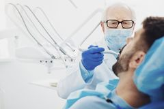 Concentrated male dentist removing teeth decay royalty free stock photo