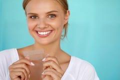 Teeth Whitening. Beautiful Smiling Woman Holding Whitening Strip Royalty Free Stock Photos