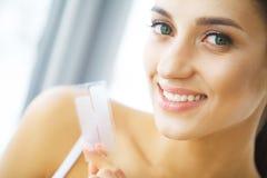 Teeth Whitening. Beautiful Smiling Woman Holding Whitening Strip. High Resolution Image Royalty Free Stock Image