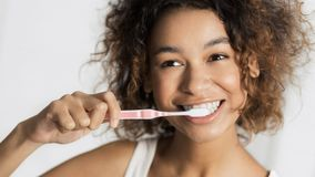Teeth whitening concept. Smiling young afro woman with toothbrush cleaning teeth at bathroom. Teeth whitening concept royalty free stock image