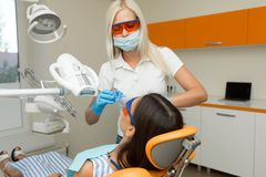 Teeth whitening by dental UV whitening device,dental assistant taking care of patient,eyes protected with glasses.Whitening treatm stock photo