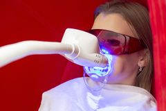Teeth whitening girl sits with apache on teeth for teeth whitening royalty free stock photography