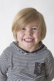 Teeth. Young boy wearing striped shirt and hood smiling at the camera Royalty Free Stock Photo