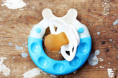 Teether and soother on wooden background. Used blue teether and used soother on rustic wooden bacground Royalty Free Stock Photos