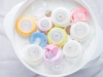 Teethers de la entrerrosca y botellas de leche en esterilizador y secador del vapor Fotos de archivo libres de regalías