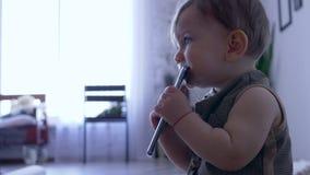 Teething, το καλό νήπιο ροκανίζει το κινητό τηλέφωνο στο δωμάτιο επάνω το υπόβαθρο απόθεμα βίντεο