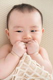 Teething Asian baby girl Stock Photo