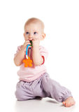 Teething baby. Teething blond baby bites colored toy on white background Royalty Free Stock Image