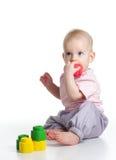 Teething baby. Teething blond baby bites colored toy on white background Stock Image