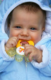 Teething baby. A teething baby boy with a toy Stock Image