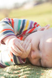 Teething: Baby Chewing on Hands. Baby wearing striped clothing lying on their side chewing on their hands and fingers stock photography