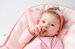 Teething baby girl. Beautiful baby girl chewing amber teething necklace royalty free stock photos