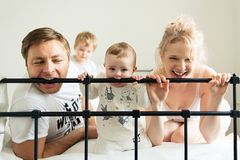 Teething baby, young family on bed. Teething baby, young family to bite bed, funny morning, copy space Royalty Free Stock Photos