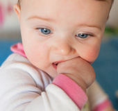 Teething concept. Baby girl with finger in mouth. Stock Photo