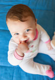 Teething concept. Baby girl with finger in mouth. Royalty Free Stock Images