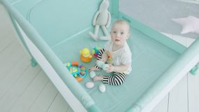 Teething infant biting toy eggs in playpen at home stock video