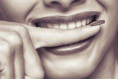 Teeths brancos que mordem um dedo Foto de Stock Royalty Free
