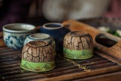Teezeit in ländlichem Vietnam - alte Teeschalen auf einem hölzernen Umhüllungsbehälter Lizenzfreies Stockfoto