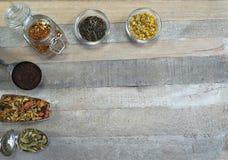 Teezusammenstellung an den Löffeln und in Glas an am hölzernen Hintergrund stockfotografie