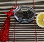 Tefat med sidor av te och snittcitronen på en filt Royaltyfri Foto