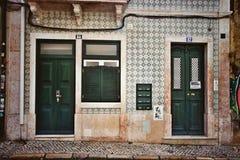 Tegelmuur met groene deuren in Lissabon stock fotografie