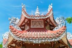 Tegelplattatak av den asiatiska templet med ljusa kulor med garnering arkivbild