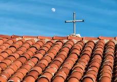 Tegelplattatak och lantligt kors på historisk kyrka arkivbilder
