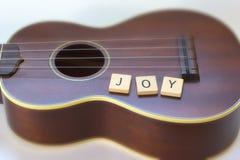 Tegelplattor för bokstav för fyrkant för selektiv fokus för ukuleleglädje på vit Arkivbilder