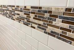 Tegelplattor som göras av exponeringsglas och stenen som installeras på väggen som garnering- eller kökbacksplash fotografering för bildbyråer