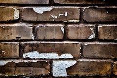 Tegelsten är inte en ideal gammal vägg med spruckna chiper arkivfoto